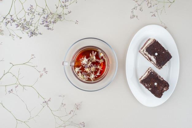 Twee plakjes tiramisu cake en kopje thee op wit oppervlak