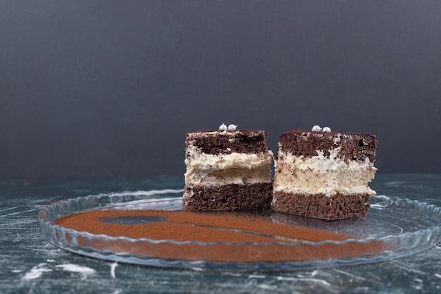 Twee plakjes tiramisu-cakes op blauwe ruimte.