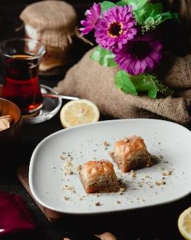 Twee plakjes turkse dessertpakhlava met een glas thee en citroenplak.