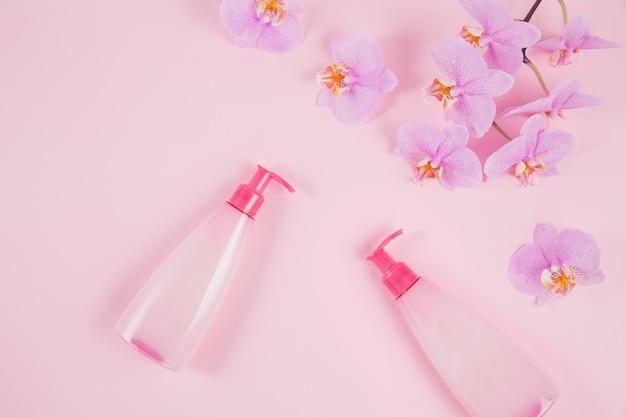 Twee plastic dispenserflesjes met vloeibare cosmetische zeep, intieme was- of douchegel en roze orchideebloemen op lichtpaars oppervlak