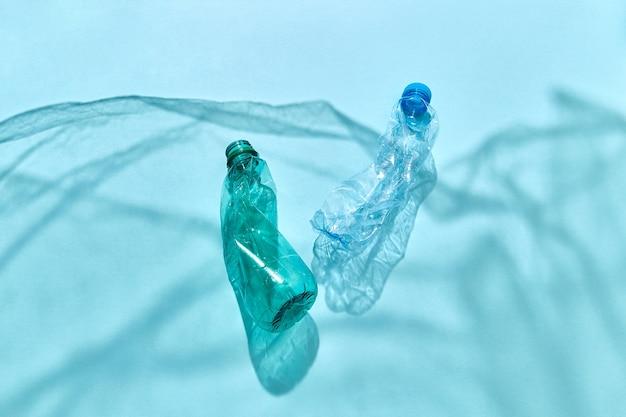 Twee plastic gebruikte flessen die in de oceaan drijven schaduwen golven van polyethyleenfolie met exemplaarruimte. concept van milieuverontreiniging van de wereldoceaan.