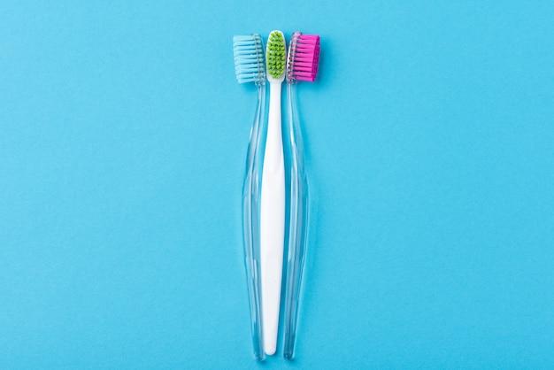 Twee plastic kleurrijke tandenborstels op blauw, sluiten omhoog