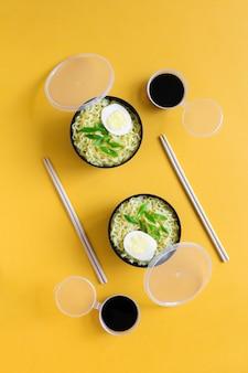 Twee plastic kommen instant noedels met eieren sojasaus eetstokjes plat lag op gele achtergrond