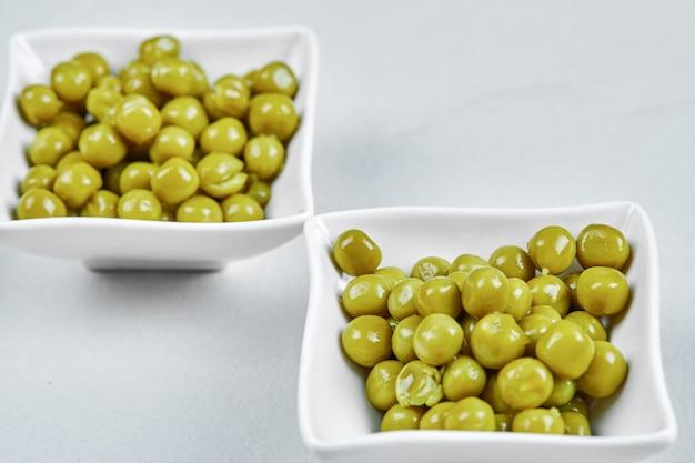 Twee platen van gekookte groene erwten op een grijze tafel.