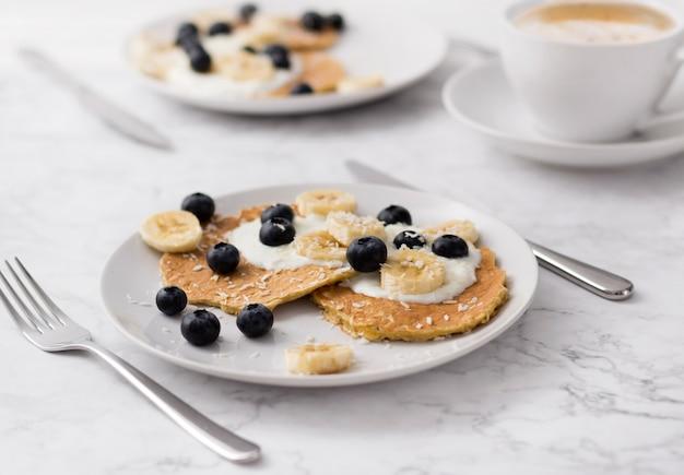 Twee platen van zelfgemaakte ontbijt met bosvruchten en kopje koffie aan marmeren tafel.