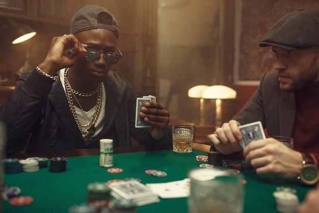 Twee pokerspelers met kaarten zitten aan speeltafel met groene doek in casino. verslaving, risico, gokhuis