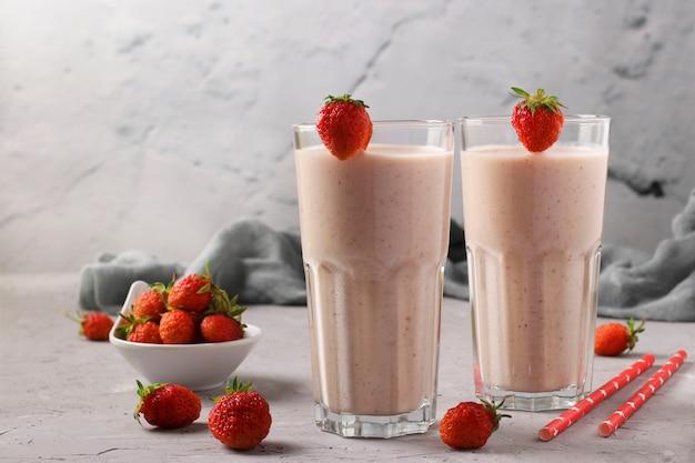 Twee porties zelfgemaakte eiwitcocktail met verse aardbeien en yoghurt in glazen op grijs