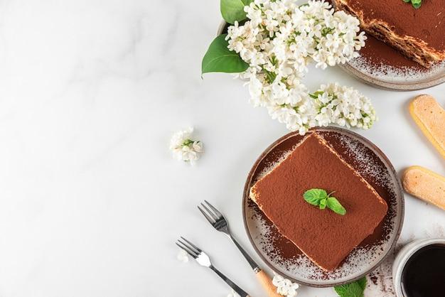 Twee porties zelfgemaakte traditionele italiaanse desserttiramisu in borden met koffiekopje, dessertvorken en bloemen op witte ondergrond voor een smakelijk ontbijt