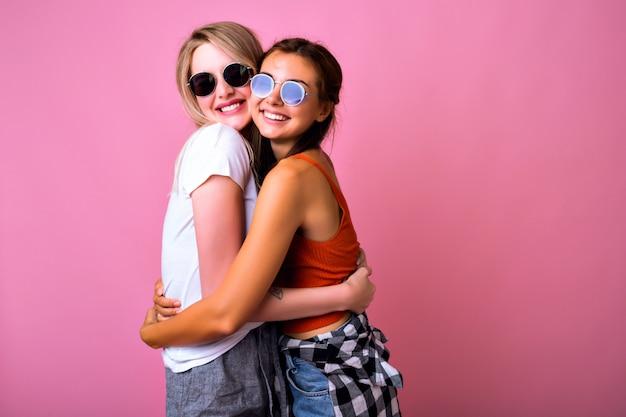 Twee positieve beste vrienden die plezier hebben met het dragen van een zonnebril