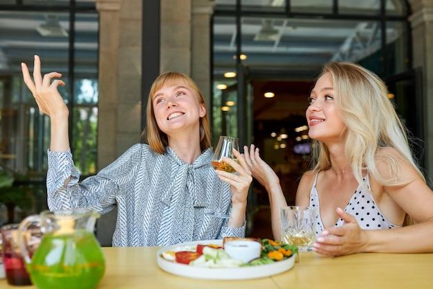 Twee positieve blanke vrouwen brengen graag tijd samen door in een restaurant