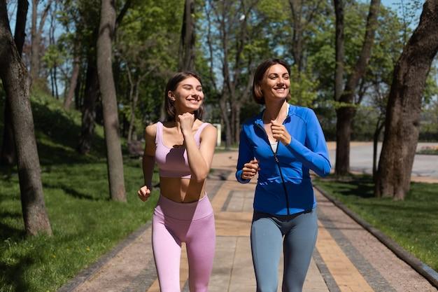 Twee positieve gelukkige vrouwenvrienden die samen joggen in parkpad lopen glimlachen en lachen