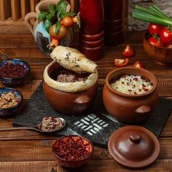 Twee potten van aardewerk met rijst en gehakt bedekt met deeg korst