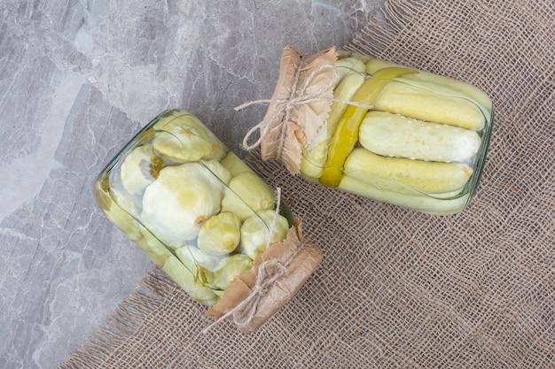 Twee potten van diverse ingemaakte groenten op jute.