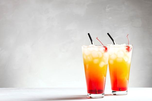 Twee prachtige cocktails van tequila sunrise op een grijze betonnen achtergrond