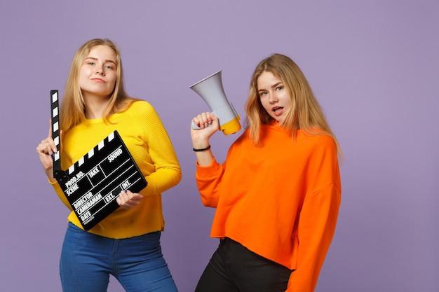 Twee prachtige jonge blonde tweelingzusters meisjes houden klassieke zwarte film filmklapper, schreeuwen op megafoon geïsoleerd op violet blauwe muur. mensen familie levensstijl concept.