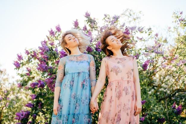 Twee prachtige levensstijl opgewonden zussen hebben plezier buitenshuis in lila struiken. tweeling jonge gelukkig lachende meisjes modellen houden handen en schuddende hoofden.