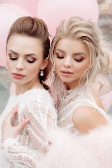 Twee prachtige modellen met make-up en kapsel in het wit.