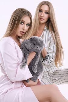 Twee prachtige modelmeisjes in pyjama poseren met een dikke raskat
