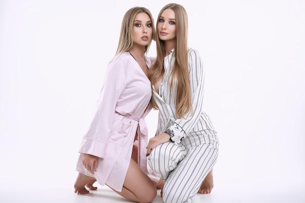 Twee prachtige modelmeisjes in pyjama