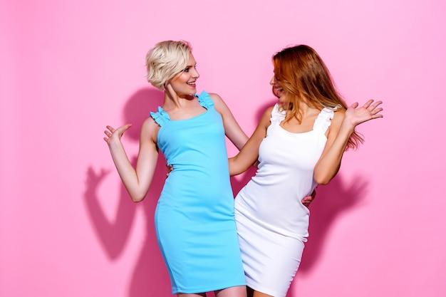 Twee prachtige mooie zelfverzekerde dame chic knuffelen met mooie leuke schattige jurken geïsoleerd op roze...