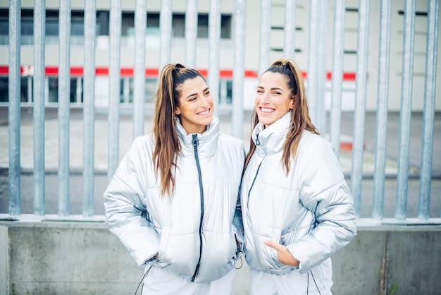Twee prachtige tweelingzusjes poseren vreugdevol op camera