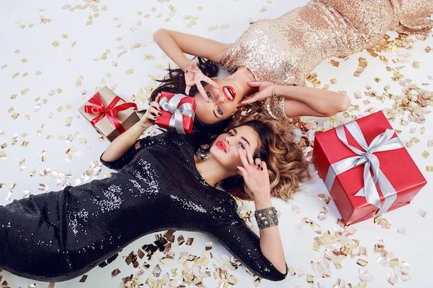 Twee prachtige verleidelijke vrouw in trendy pailletten jurk liggend op witte vloer met glanzende gouden confetti en rode geschenkdozen
