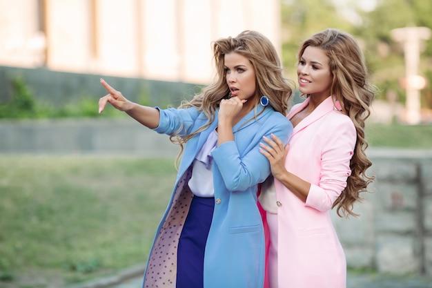 Twee prachtige zakelijke vrouwen staan en ergens kijken