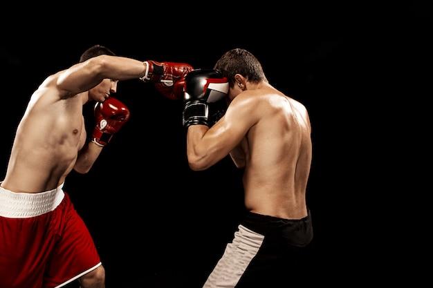 Twee professionele bokser boksen op zwart,