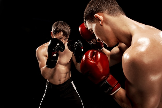 Twee professionele bokser boksen op zwarte achtergrond,