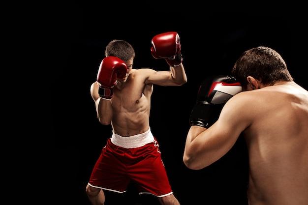 Twee professionele bokser boksen op zwarte muur,