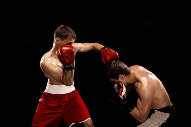 Twee professionele bokser boksen op zwarte rokerige achtergrond,