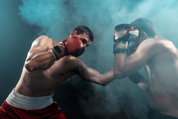 Twee professionele bokser boksen op zwarte rokerige ruimte,