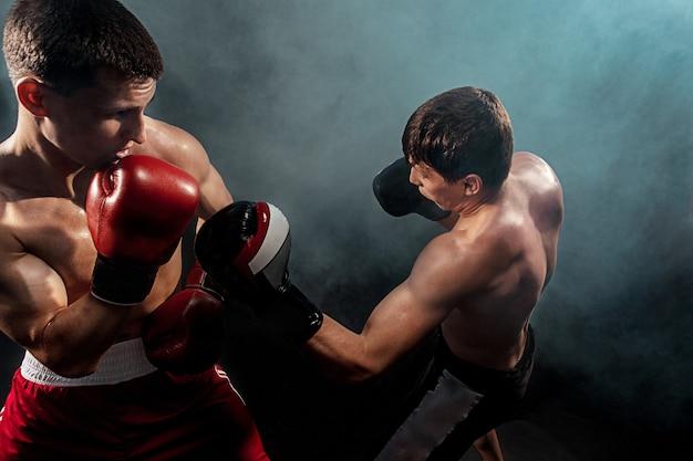 Twee professionele bokser boksen op zwarte rokerige studio achtergrond.