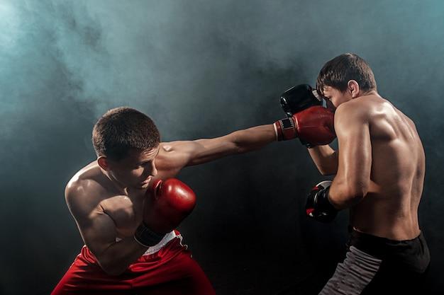 Twee professionele bokser boksen op zwarte rokerige