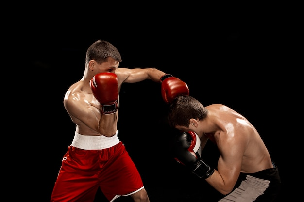 Twee professionele bokser boksen op zwarte ruimte,