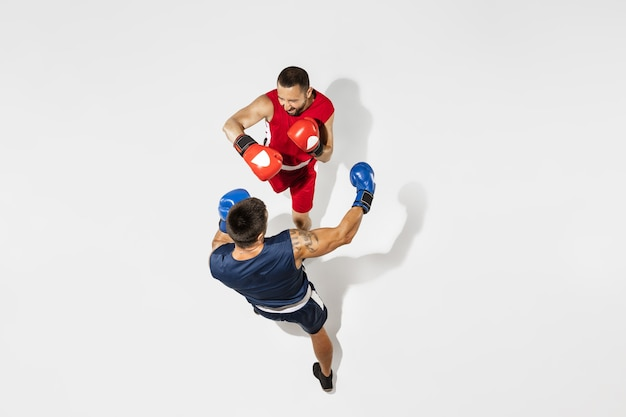 Twee professionele boksers boksen geïsoleerd op een witte studio achtergrond, actie, bovenaanzicht. paar fit gespierde blanke atleten vechten. sport, competitie, opwinding en menselijke emoties concept.