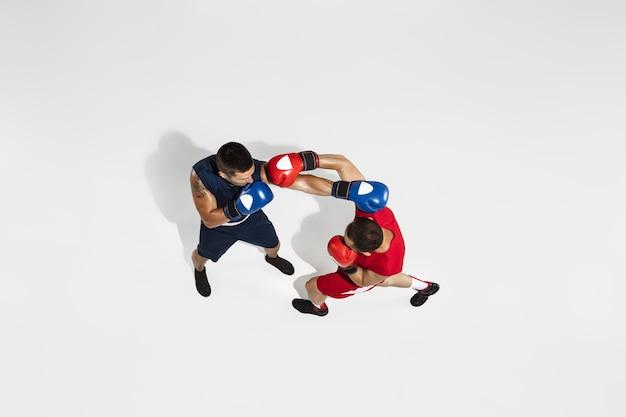 Twee professionele boksers boksen geïsoleerd op een witte studio achtergrond actie bovenaanzicht