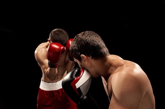 Twee professionele boksers die op zwarte muur in dozen doen