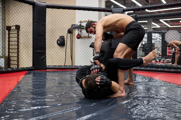 Twee professionele boksers in dynamische boksactie op de ring in de sportschool. boxer sloeg tegenstander, maakte verschillende vechttrucs, sportconcept
