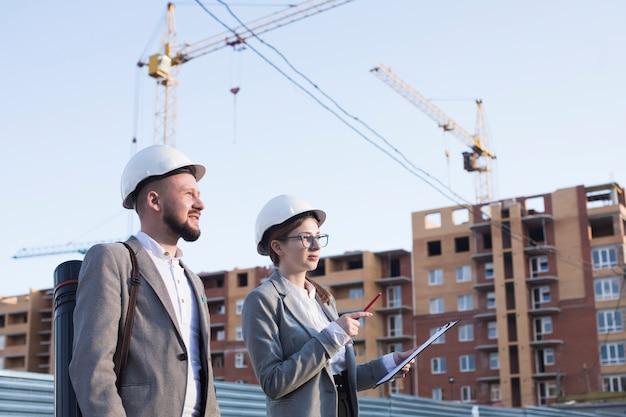 Twee professionele ingenieur die aan bouwwerf werkt