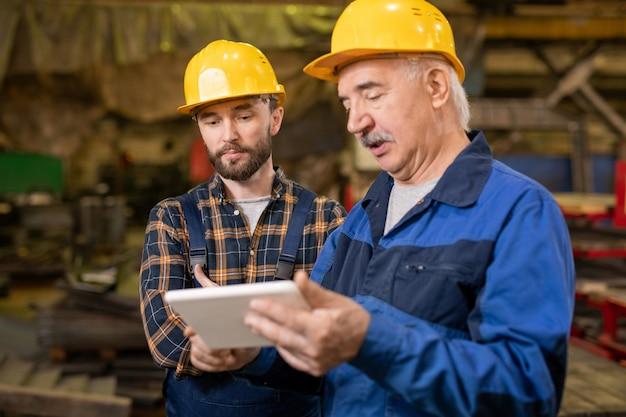 Twee professionele ingenieurs in helmen en werkkleding kijken naar tablet-display terwijl technische gegevens worden besproken