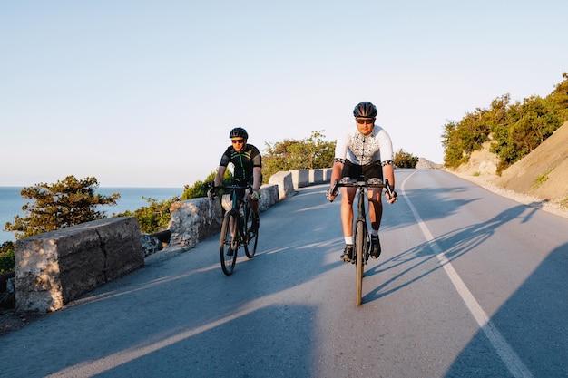 Twee professionele mannelijke fietsers rijden hun racefietsen in de ochtend samen op kustweg