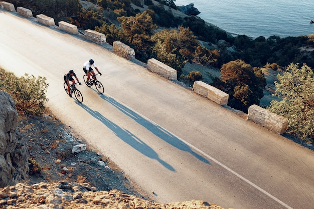 Twee professionele mannelijke fietsers rijden op hun racefietsen