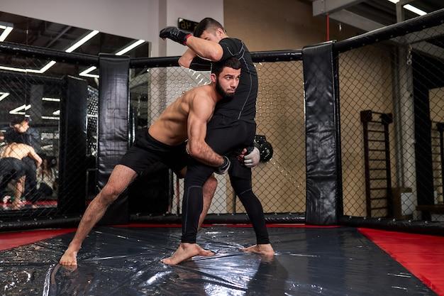 Twee professionele mma-vechters boksen in actie. gespierde atleten. sport, gezonde levensstijl, competitie, dynamiek en beweging, actieconcept. kopieerruimte. zijaanzicht