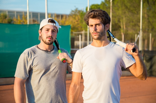 Twee professionele tennisspelers met jongens met een hard gezicht op een tennisbaan.