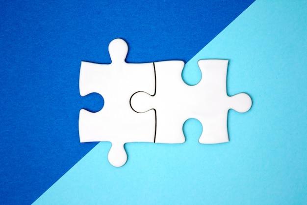 Twee puzzelstukjes verbinden elkaar op blauw geometriekleurpapier.