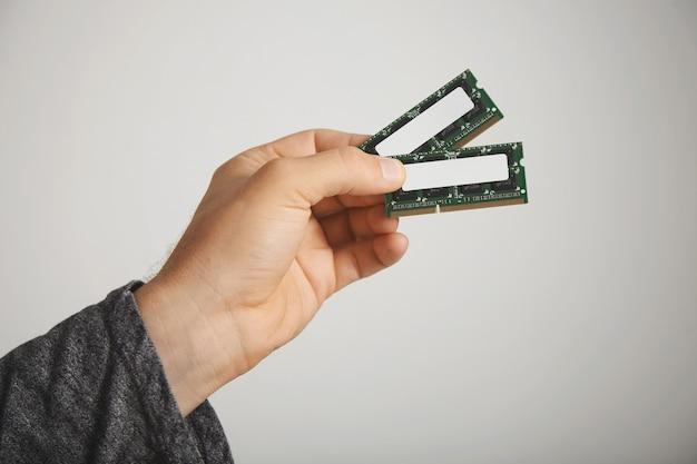 Twee ram-chips in de hand van een man op wit wordt geïsoleerd
