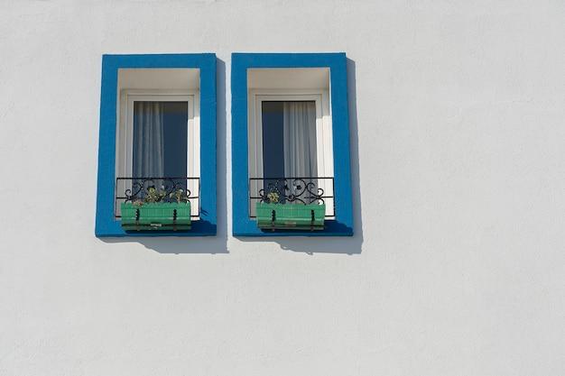 Twee ramen met bloempotten op witte muur in bodrum, turkije, kopieer ruimte