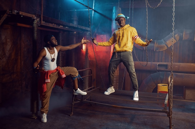 Twee rappers poseren, optreden in coole studio, ondergrondse decoratie. hiphopartiesten, trendy rapzangers, breakdancers