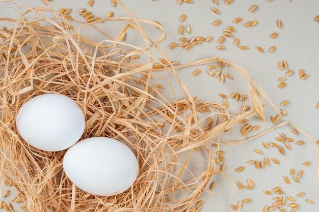 Twee rauwe eieren en gerst geplaatst op vogelnest op grijze ondergrond.
